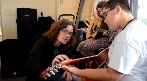 Bret Dale instructs two young students in guitar basics